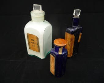 Three vintage glass apothecary bottles, two blue, one white