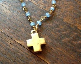 Little gold cross necklace on an aqua blue Malaysian jade rosary chain.