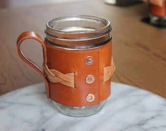 Leather mason jar sleeve.  Wide mouth 16 oz. mason jar.  Coffee mug with braid under handle.