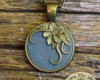 Bronze tone floral design on blue