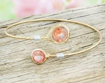Worn goldtone and rose stone bracelet