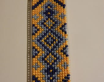 Bookmark on plastic canvas (handmade cross-stitched yellow and blue ornament).