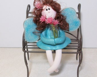 Miniature Garden Fairy figurine sitting on a metal park bench with a glass vase and flowers