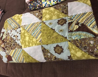 Handmade quilt in greens, soft blues, and browns. Triangle peices lay out this modern pattern.