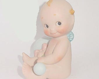 Kewpie by Enesco -Bisque  Kewpie Sitting  with Large Rattle or Dumb Bell ?  Dated 1992  -A Cutie