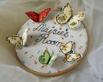 Butterfly Name Plaque freehand machine embroidery framed on a hoop with a ribbon hanging loop. 3D butterflies.