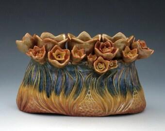 Porcelain flower brick or candle holder, carved in blue, purple, gold & orange glazes