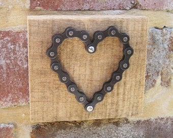 Bicycle chain heart on rustic wood