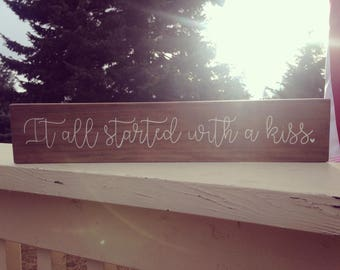 "3 1/2"" x 18"" wood sign ""It all started with a kiss"" walnut-stained painted in a creamy white with heart detail"