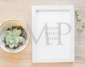 White frame mockup with green Kate Spade earrings and succulent in teacup on wood stock photo
