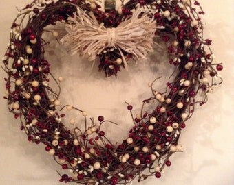 Heart-shaped grape vine rustic wreath with red and white berry vine and raffia bow