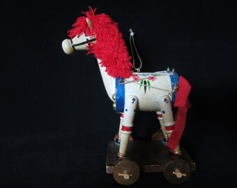 Folk-Art Wooden Horse Ornament - trunk is a replica of a drum. Has golden drum-stick tail. Bright red yarn mane, stands on rolling platform!