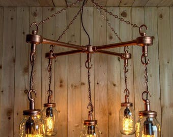 Hanging Mason jars in an 'X' formation with chains and vintage light bulbs finished in copper