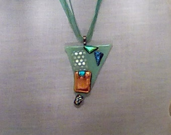 Mint green fused glass pendant with multi colored pieces of dichroic glass