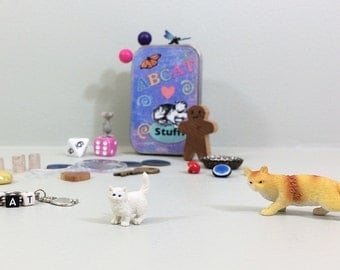 Treasure box for children with new and vintage tiny toys, including cats, charms, dice, vintage key, and random fun stuff