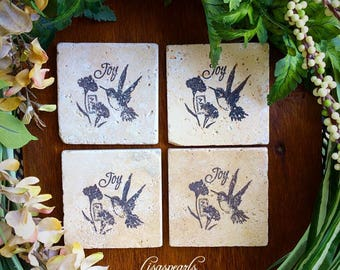 4 Hummingbird coasters with joy stamped . Travertine natural stone coasters . 4x4 inches. Inspirational coasters .