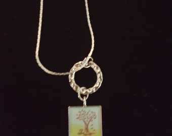Cute and dainty Tree pendant with birds hanging on a silver textured ring. on Sterling silver necklace