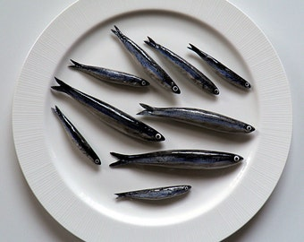 Hand-painted ceramic molded and anchovies served on porcelain plate. Porcelain plate decorated with composition of fish.