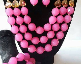 A women pink white and gold chunky beaded necklace earrind and bracelet set