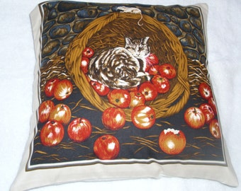 A brown tabby cat in a basket of apples cushion
