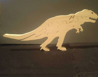 This is a scroll sawn wooden tyrannosaurus rex puzzle