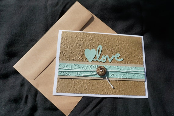 Embossed teal and brown love card with coconut button.