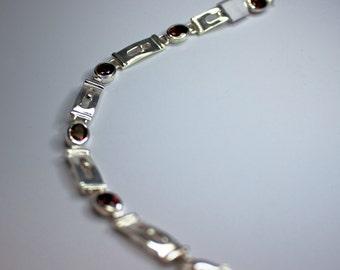 Silver bracelet set with red garnet