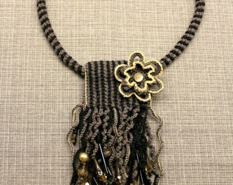 Knitted pendant with flower, black and brown, cotton yarn, beads.