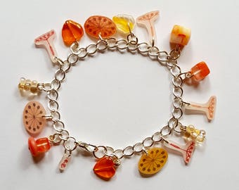 Orange and silver charm bracelet with glass beads and shrink plastic charms