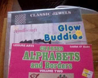Three  Counted Cross Stitch pattern booklets--themes are  jewelry, alphabets, borders,  plastic canvas whimsical  animals