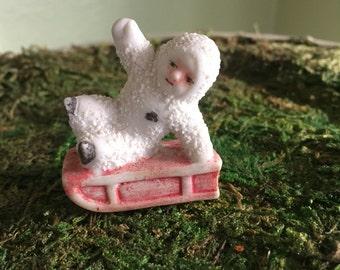 Sledding snow baby miniature figurine