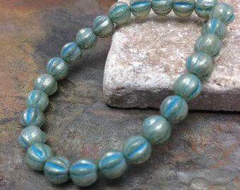 Czech Glass Melon beads 6mm. One unit has 25 beads. Color: milky aqua with mercury glass finish look and turquoise wash