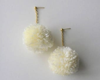Pom-pom drop earrings dangling on on gold chain and gold stud in cream