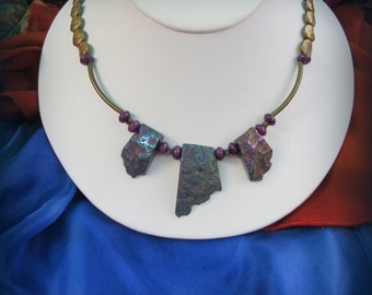 Amethyst and iridescent quartz combine with brass on this statement necklace