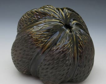 Large bronze carved porcelain pod with dark celadon glaze