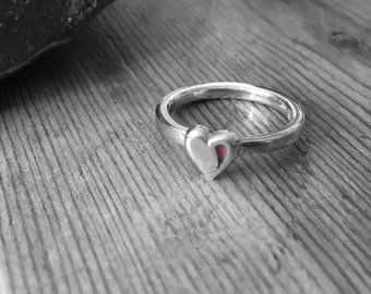 Silver ring with a silver heart that has a red enamel highlight.