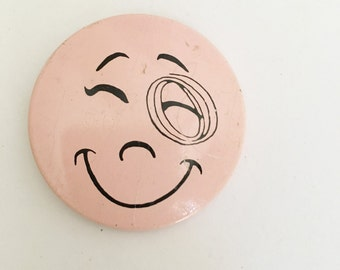 vintage pink creative house winking eye pinback button 60641 made in usa