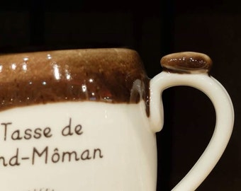 The grand-môman mug (grandmother's version in Quebec) . It has a bird pattern on the front of the cup and behind a book with glasses.