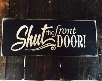 6x14 hand painted wood sign. Shut the front door!! Funny, cute sign Done in black with white lettering. Hung with a sawtooth hanger, sealed