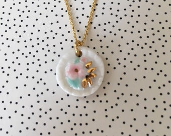 white porcelain pendant with tiny flowers with pink, green and gold details on vermeil chain