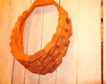Handmade, vintage wall pocket made of light color wood.