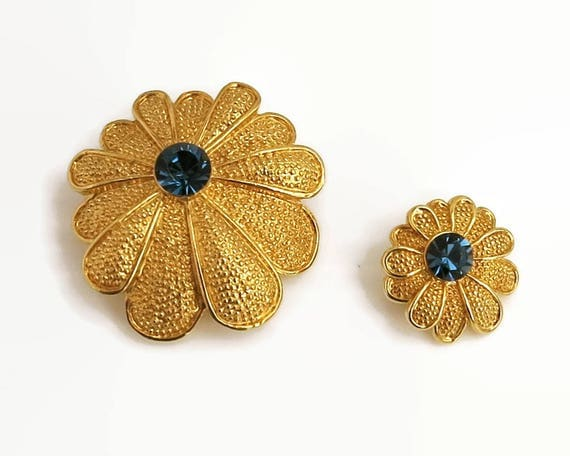 2 matching gold tone flower brooches with blue glass centers and 11 textured petals each, 2 different sizes, C-clasps, circa 1960s