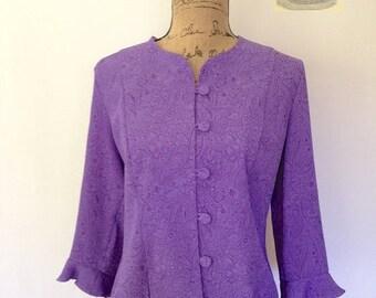 Vintage purple jacket w/ embossed paisley design. Bracelet sleeves with flounced cuff. Front hoop button enclosure. Size Medium