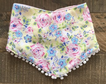 Reversible floral/pink bib with cream pom trim