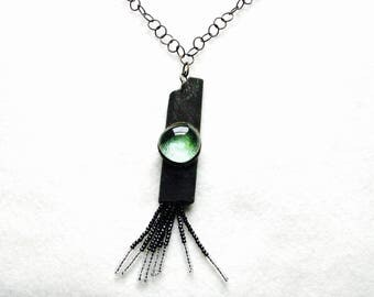 Etched metal pendant with glass bead and fringe