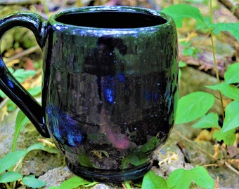Black mug with specks of blue and purple and white glitter