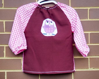 Toddler's long sleeve waterproof art smock, age 2-3 years. Dark maroon with pink check and owl motif.