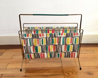 Mid century modern metal wire magazine rack with a green vinyl bag with mod pattern in greens, red, yellow and white.