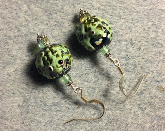 Black and light green lampwork frog bead earrings adorned with light green Czech glass beads.