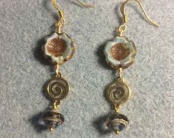 Light blue and brown Czech glass pansy bead earrings adorned with gold swirly connectors and light blue Czech glass Saturn beads.